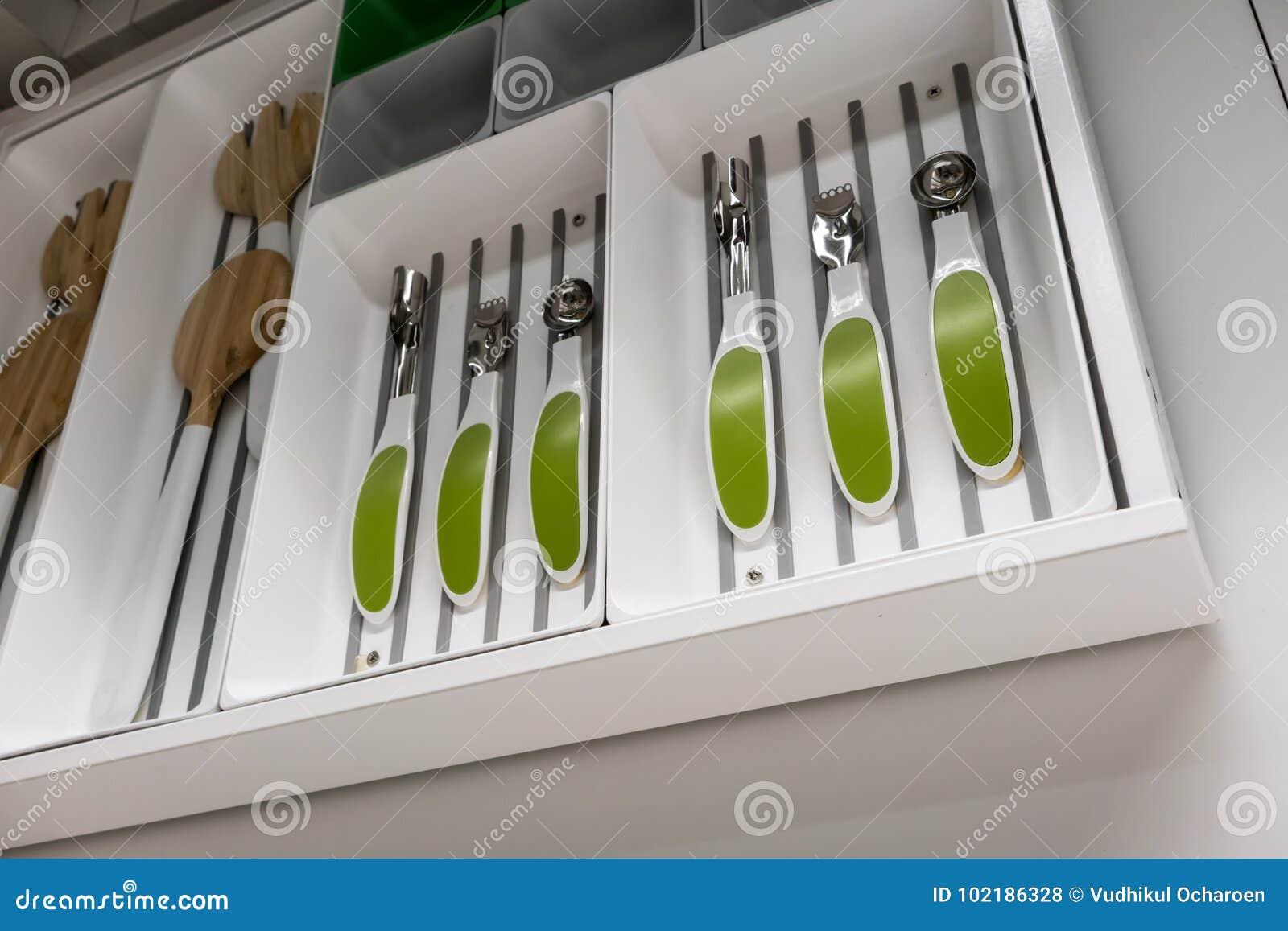 Colheres, forquilhas e utensílios da cozinha no compartimento plástico branco