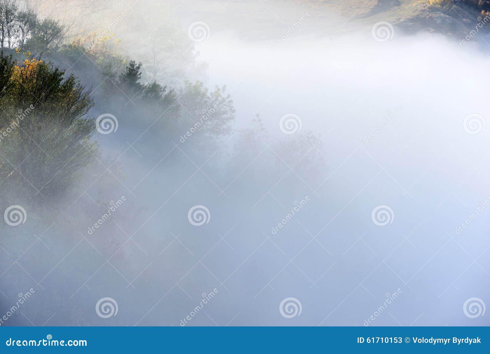 Colina en la niebla y las nubes brumosas de la salida del sol