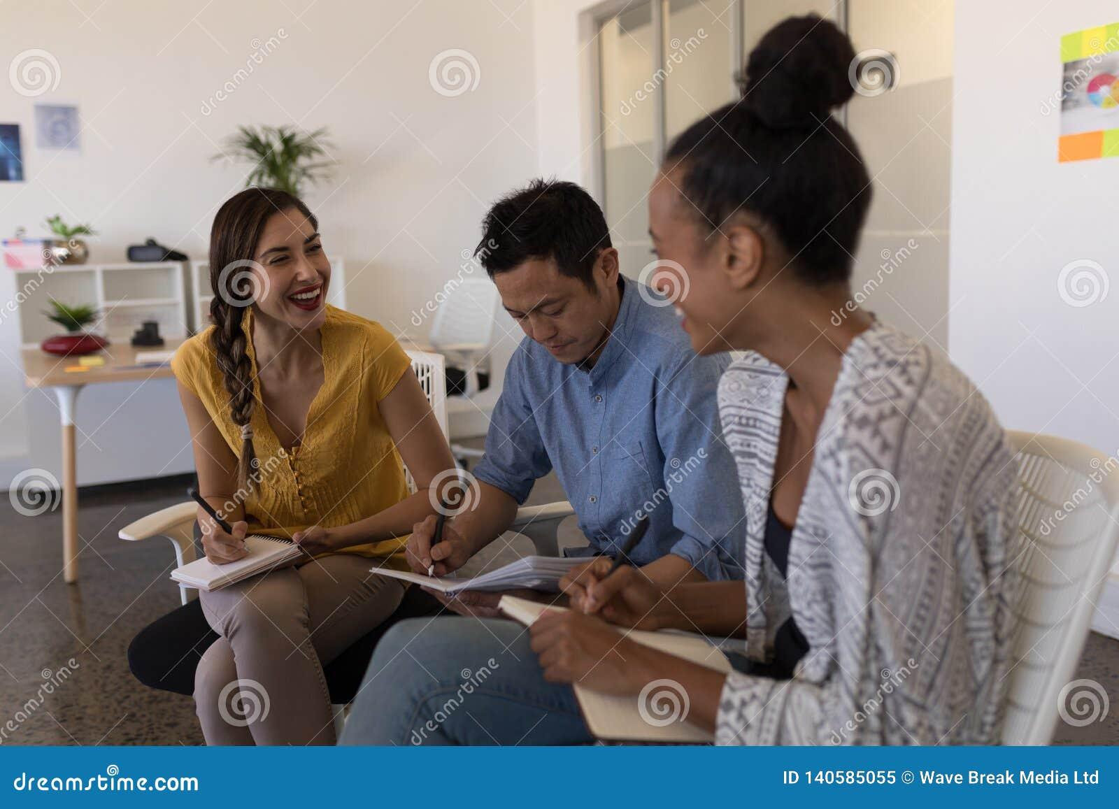 Collègues d affaires agissant l un sur l autre les uns avec les autres dans le bureau