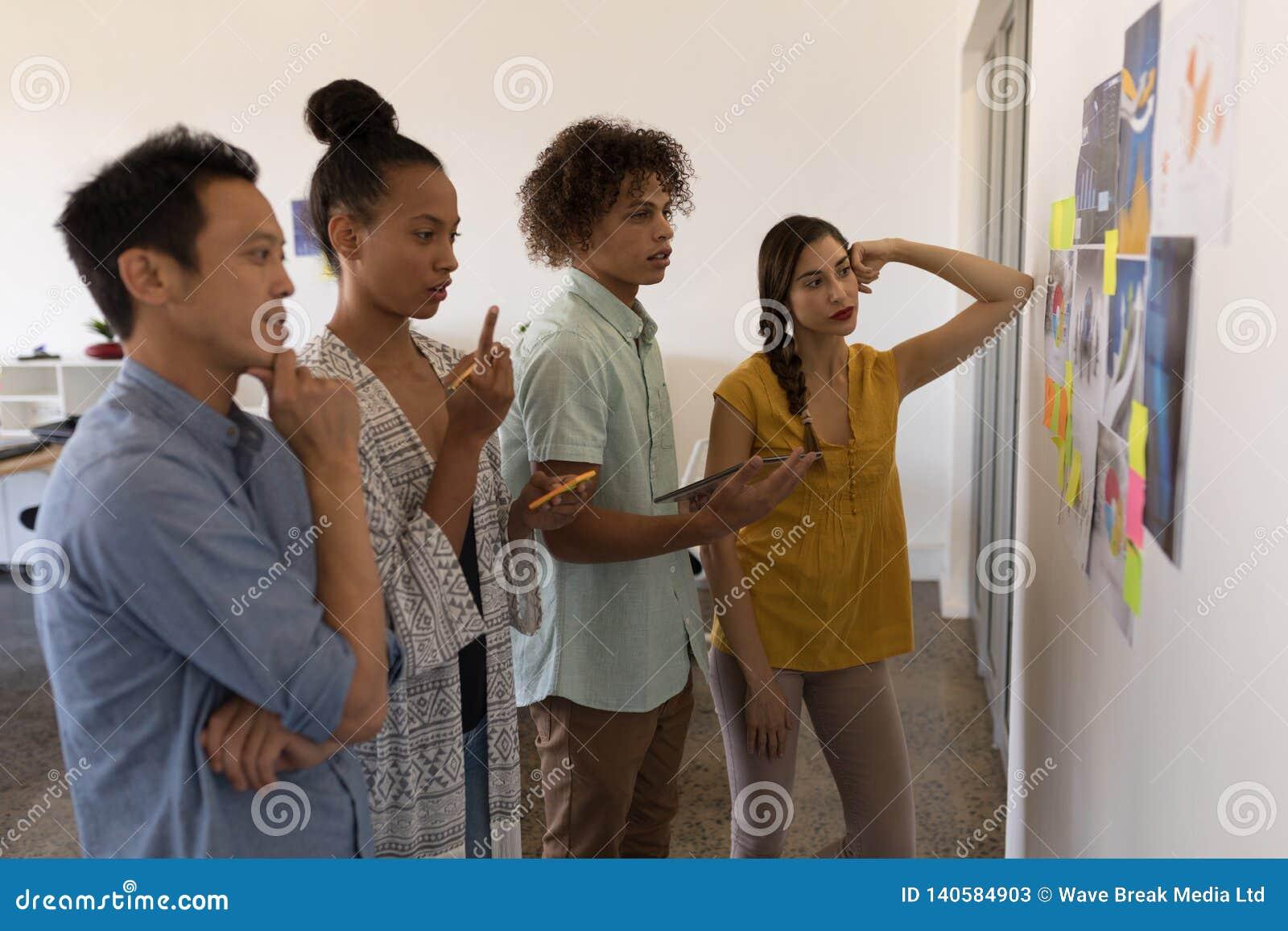 Collègues d affaires regardant des graphiques et des notes collantes dans le bureau