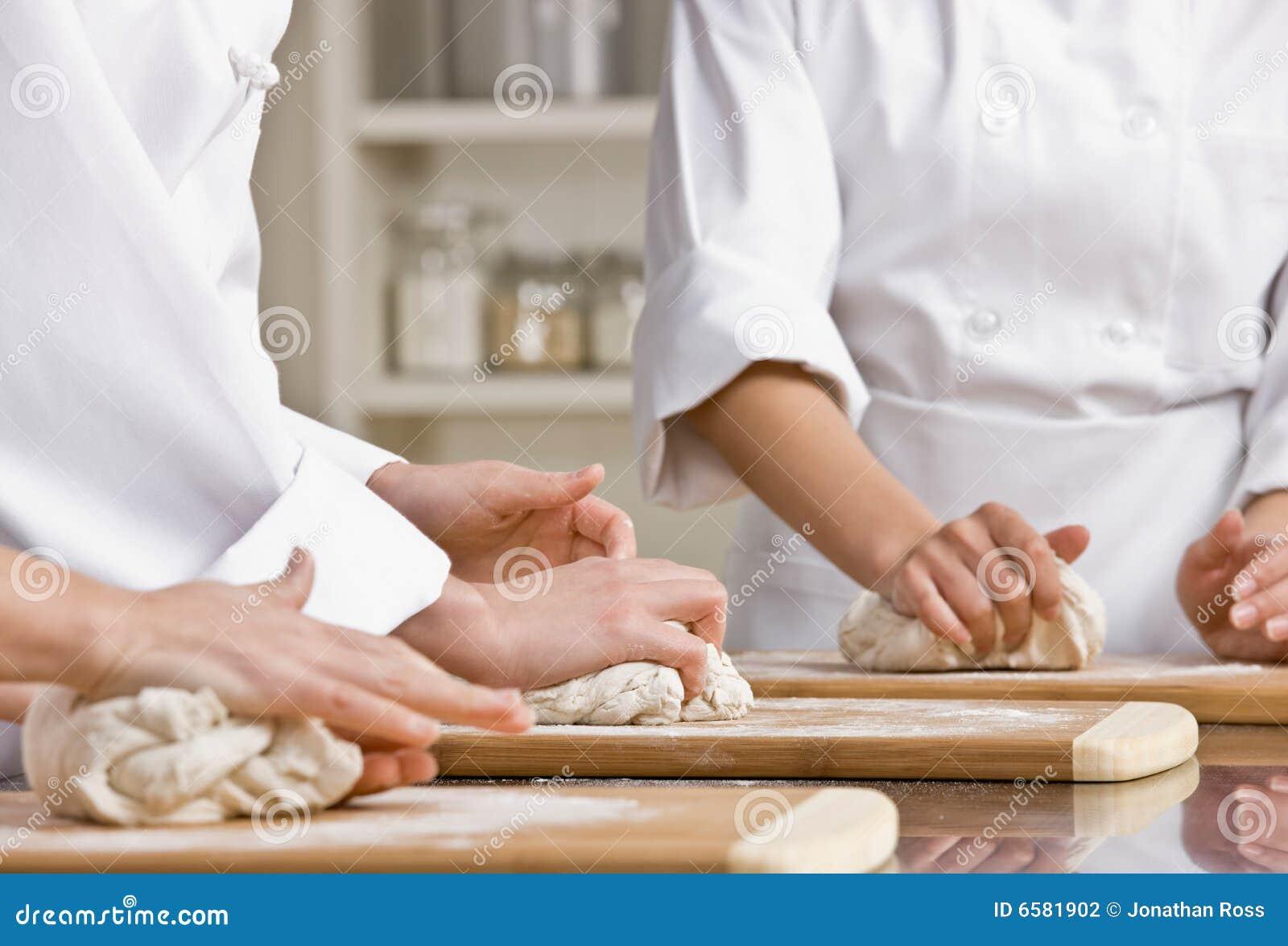 Collègues de chef malaxant la pâte dans la cuisine