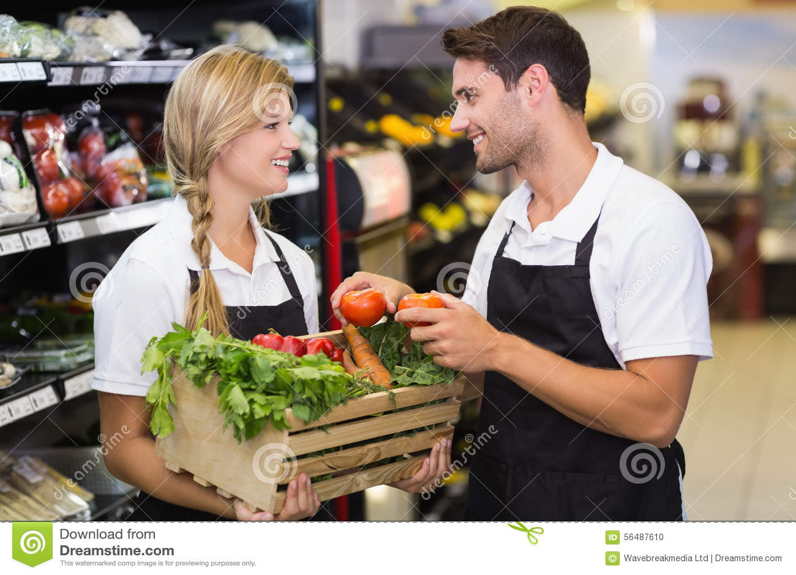 Collègues de sourire tenant une boîte avec les légumes frais