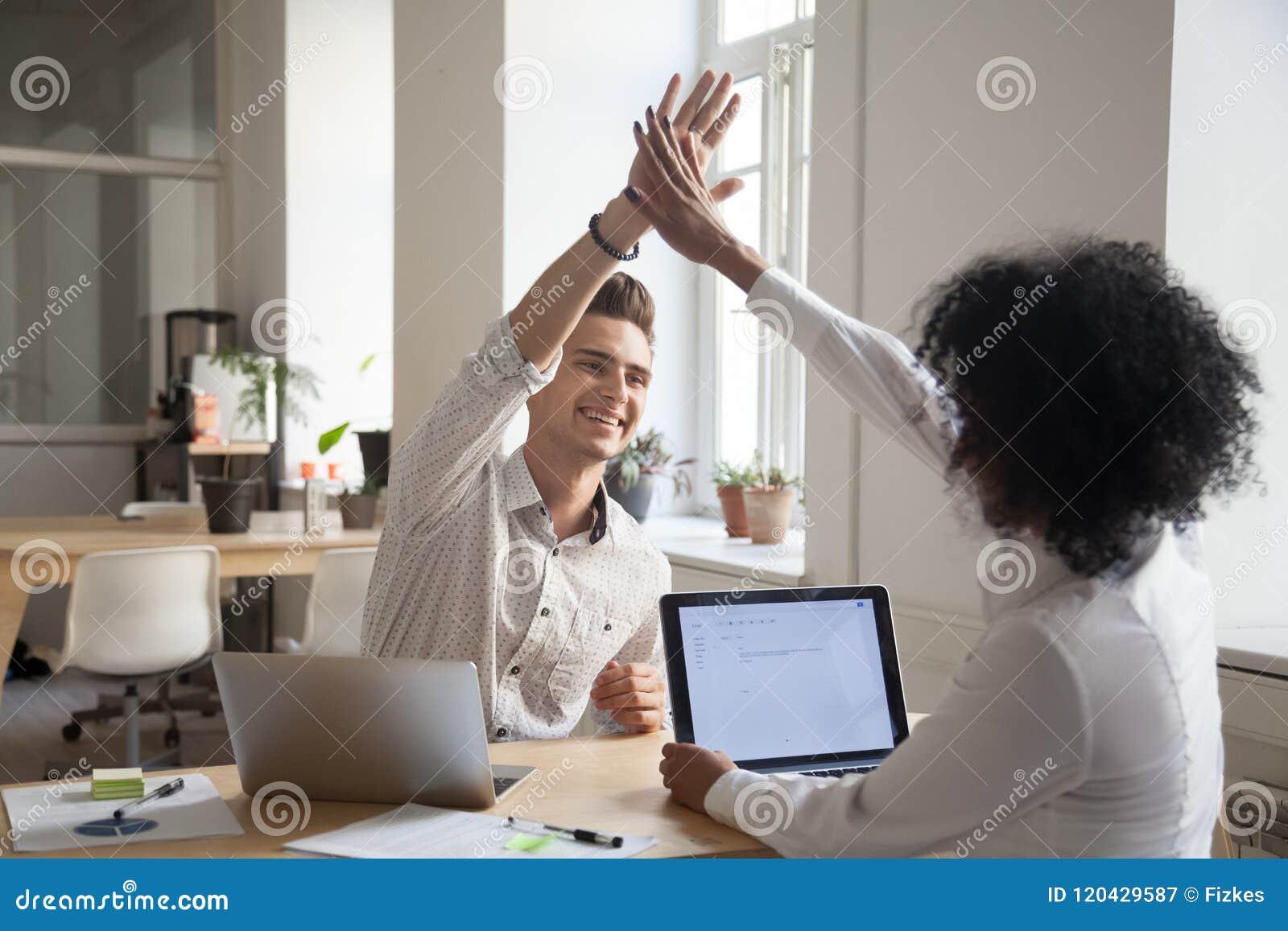 Collègues heureux donnant la haute cinq satisfaite des résultats élevés