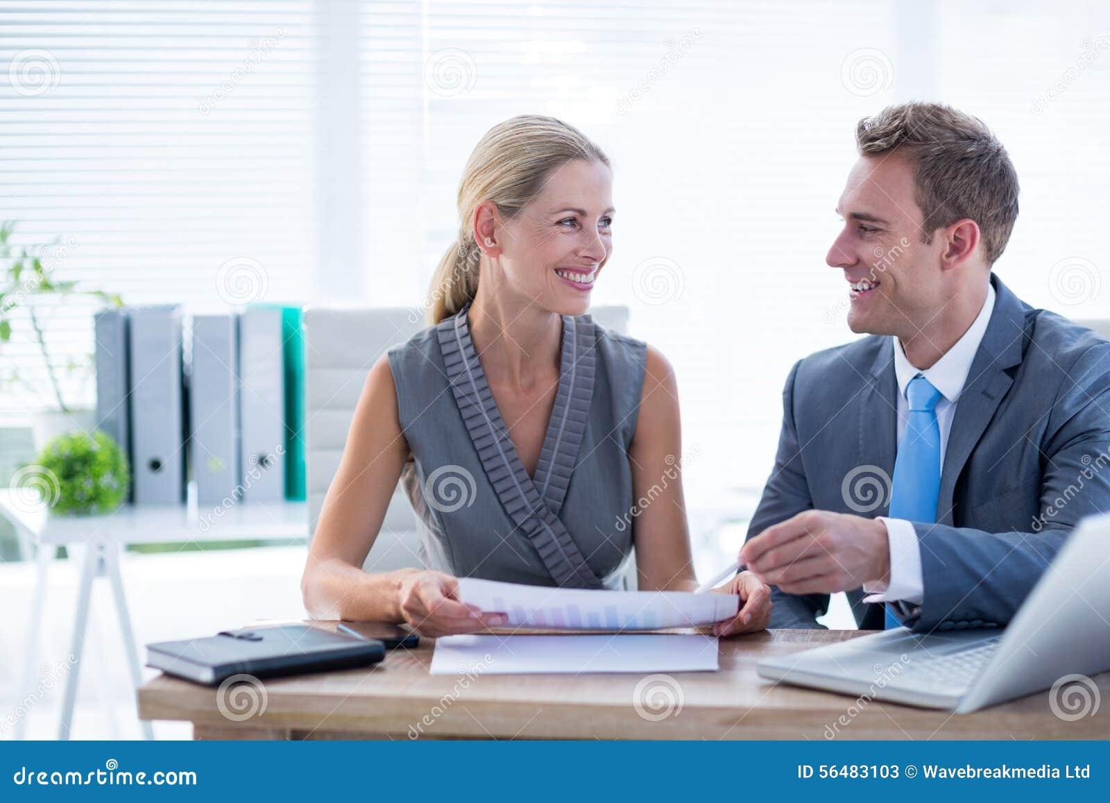 Collègues heureux travaillant ensemble sur l ordinateur portable et le dossier