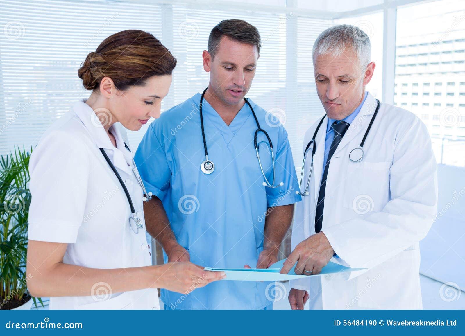Collègues médicaux concentrés analysant le dossier ensemble