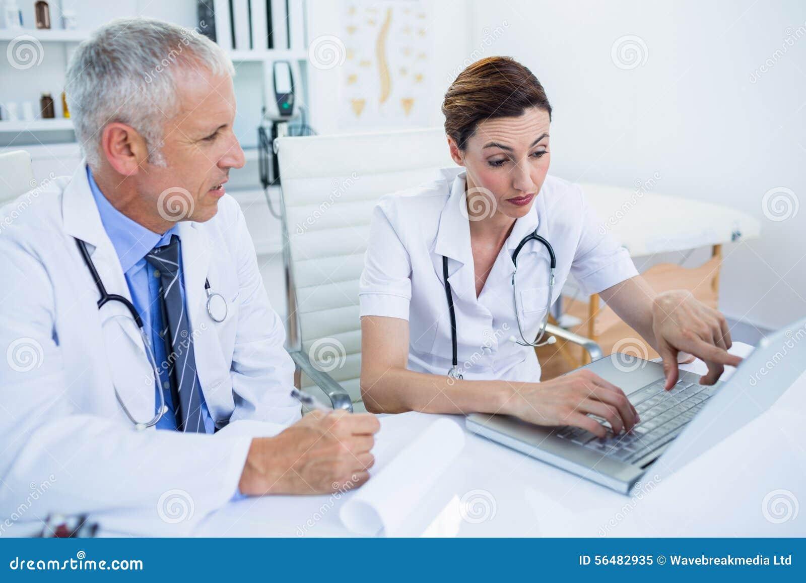 Collègues médicaux concentrés discutant et se dirigeant sur l écran d ordinateur portable