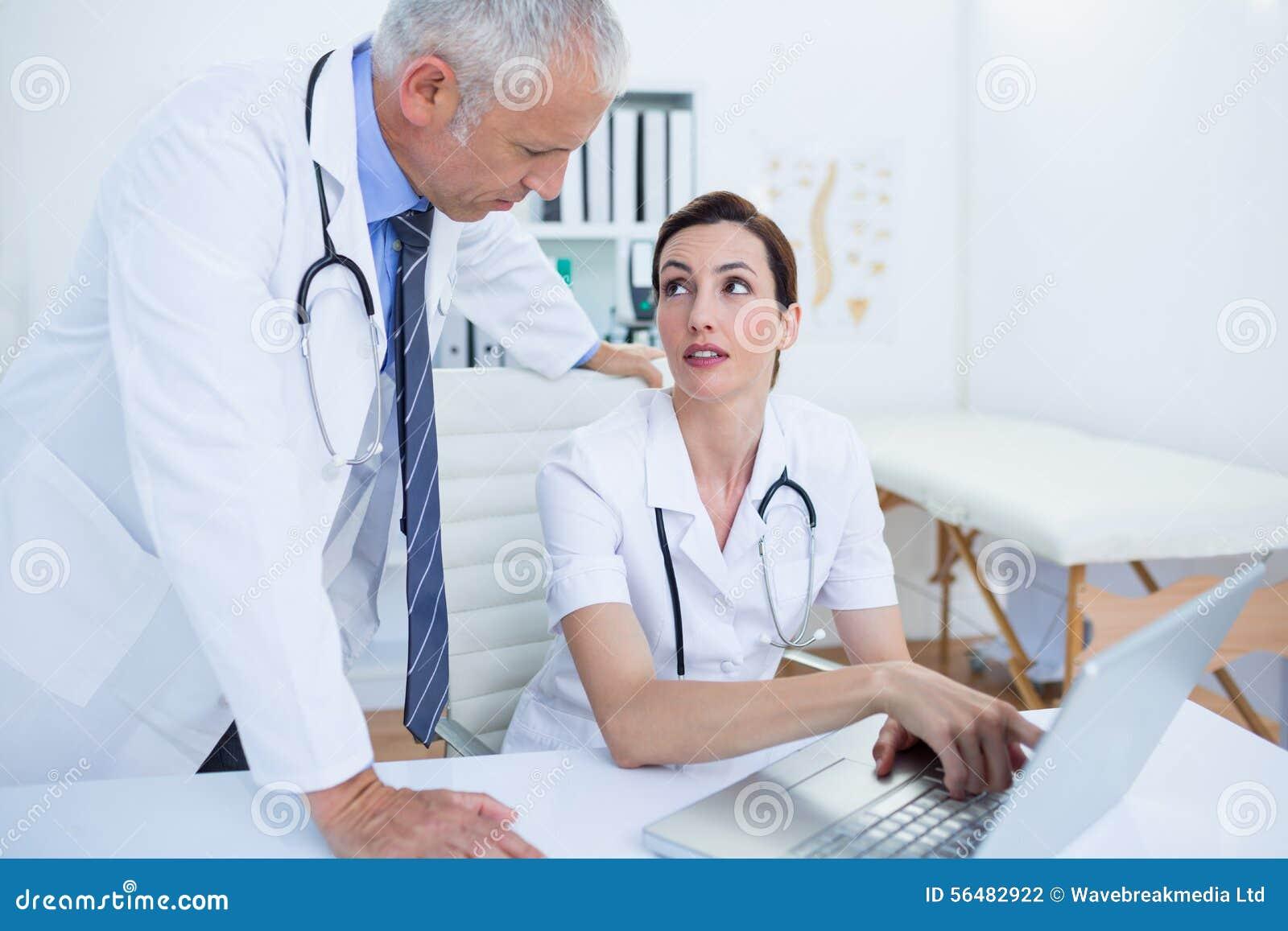 Collègues médicaux concentrés discutant et travaillant avec l ordinateur portable