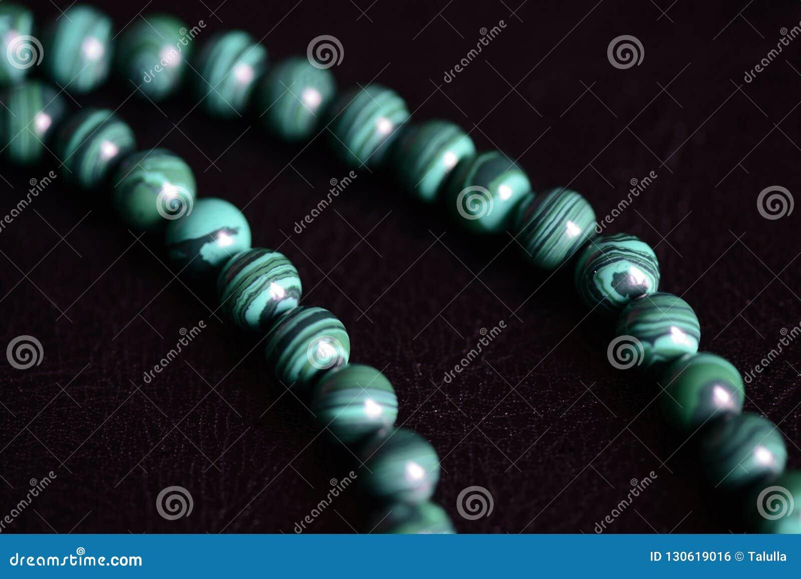 Collana di pietra delle perle della malachite su un fondo scuro