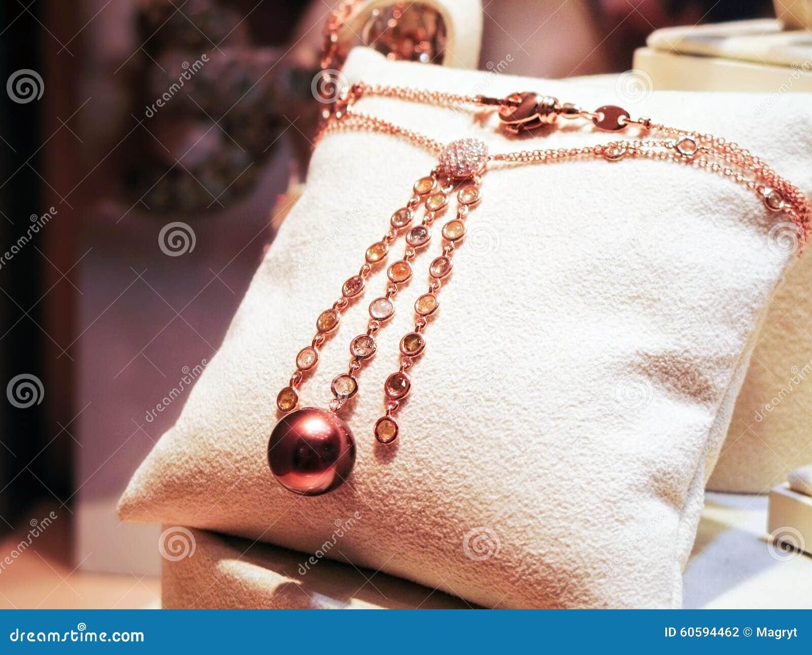 Collana fatta di oro rosa con i diamanti e le gemme