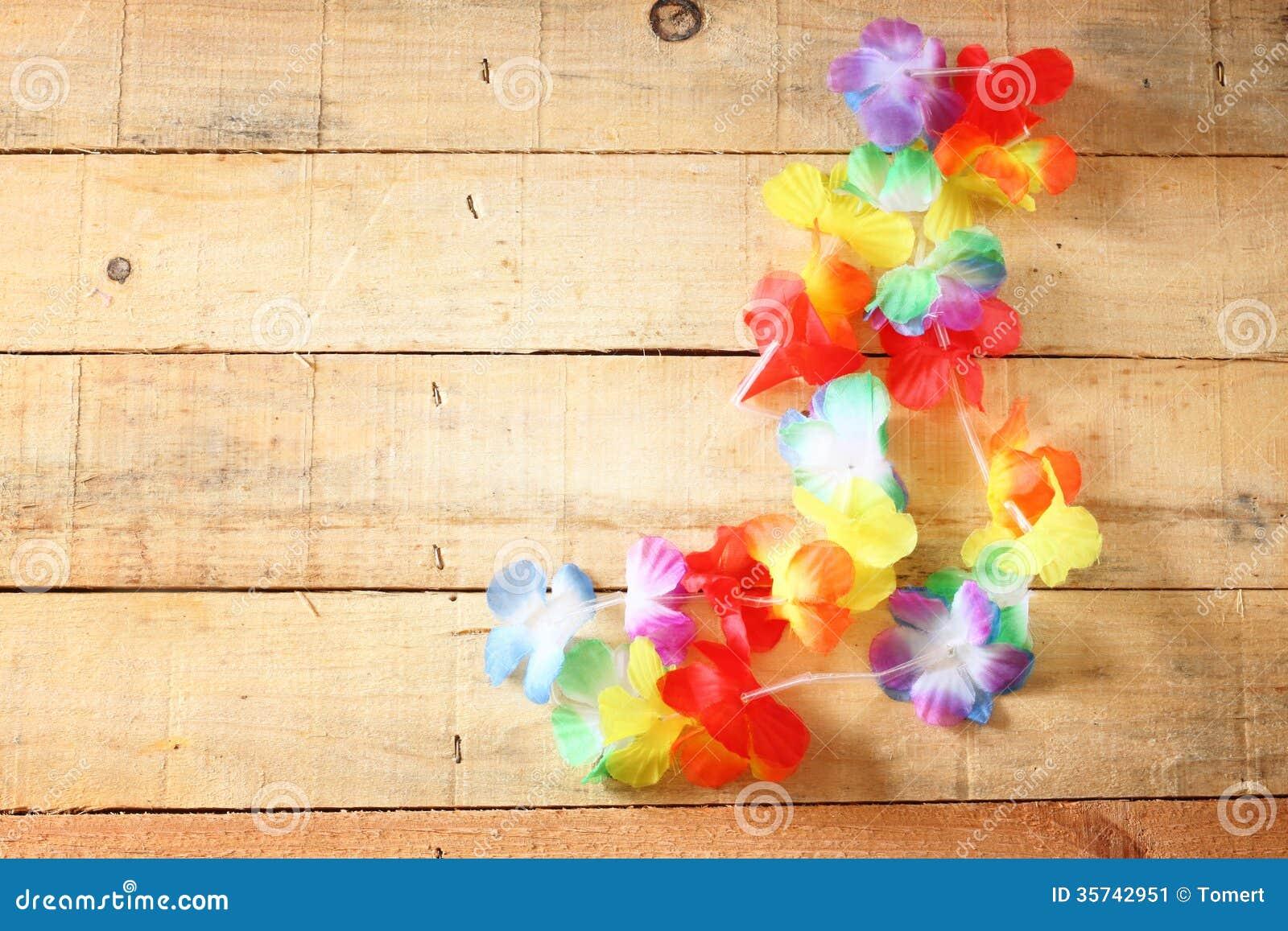 Collar de los leus coloridos brillantes de las flores en el fondo de madera