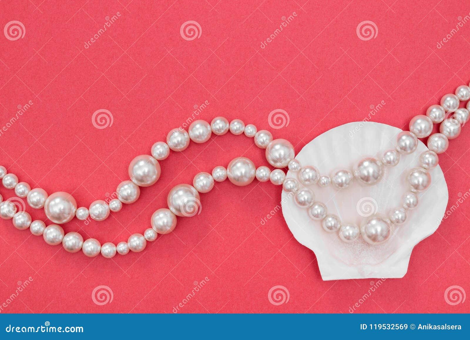 Collar y concha marina de la perla en fondo rosado