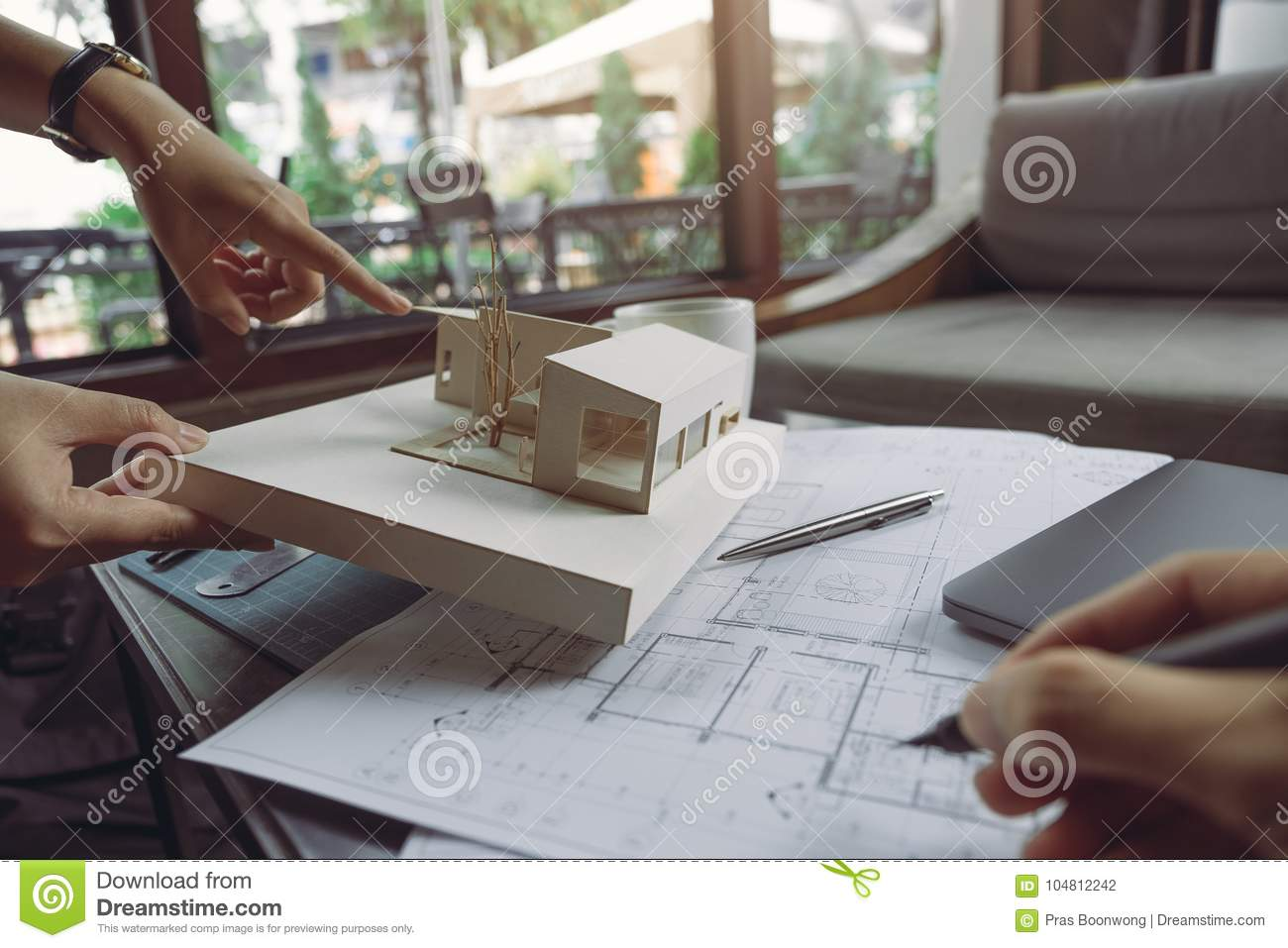 The colleague team of architects discussing and pointing at architecture model with shop drawing paper and laptop