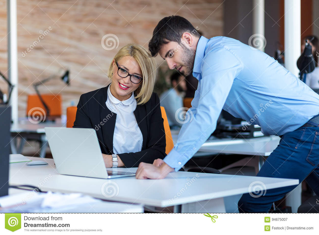 Colleagues chatting, sitting together at office table, smiling