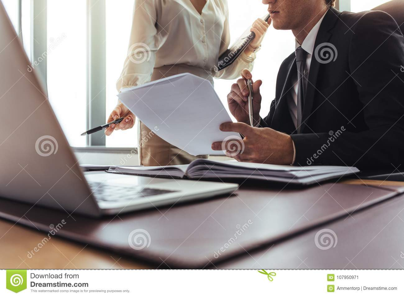 Colleagues comparing documents in office