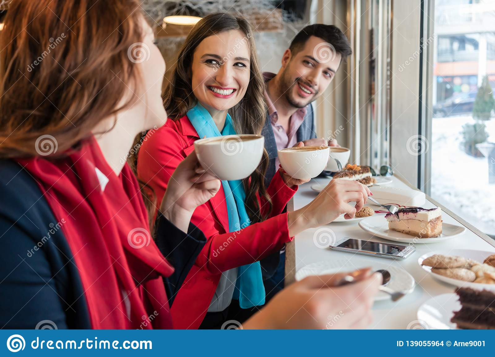 Colleagues smiling while eating delicious cakes during break in a coffee shop