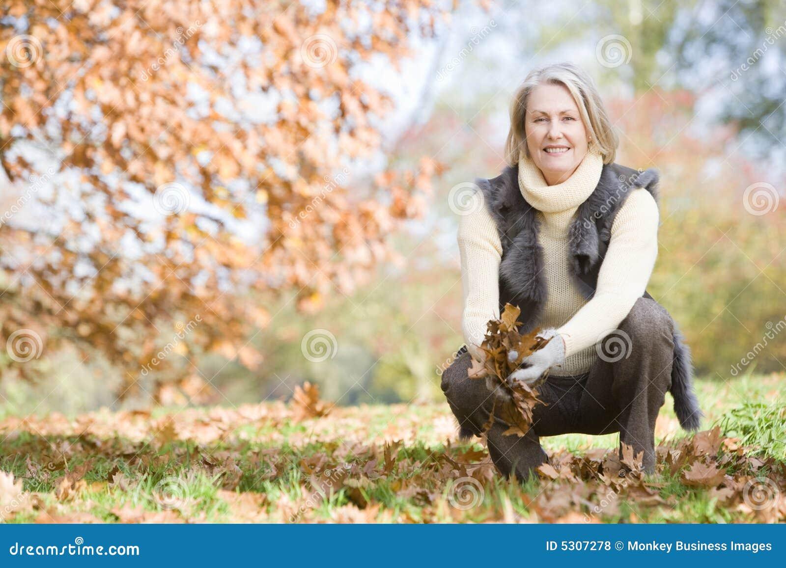 Collecting leaves senior walk woman