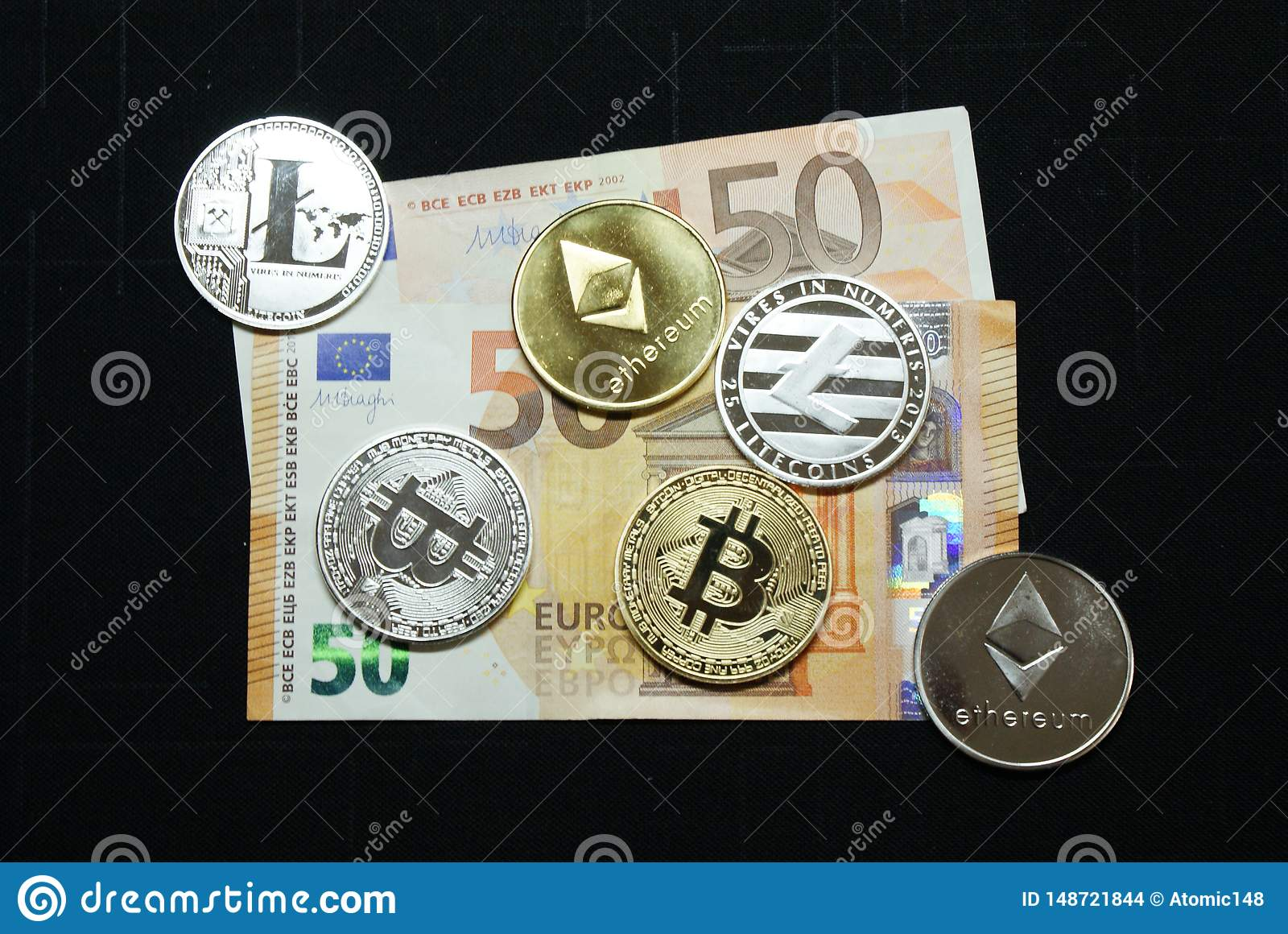 Collection of silver and gold cryptocurrency coins on a 50 euro banknote