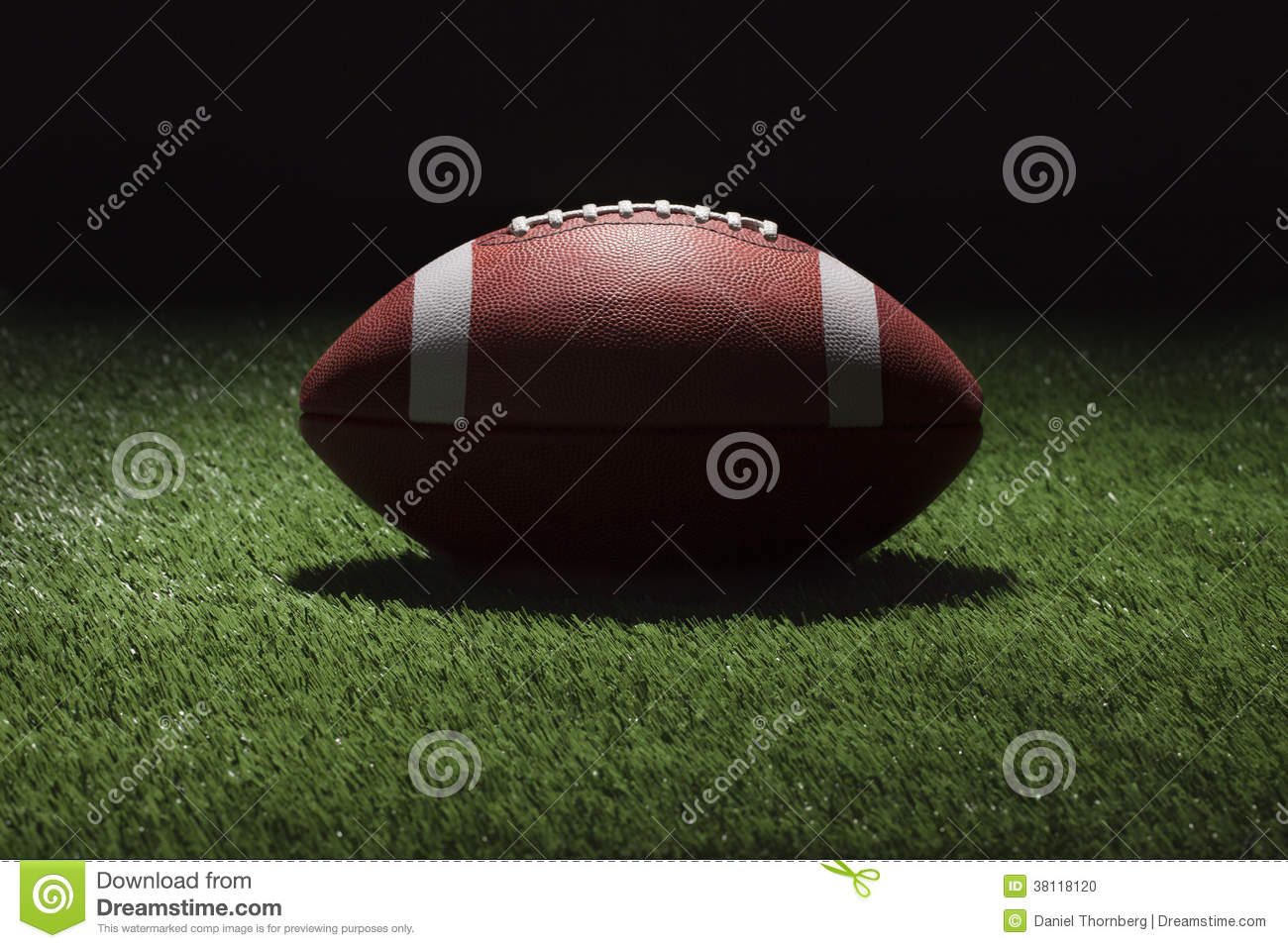 College football on grass field at night with spot lighting