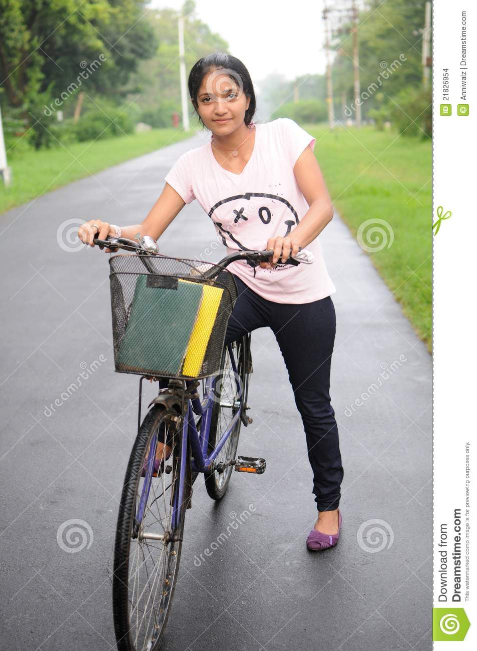 college girl on her cycle, at the middle of road. stock photo
