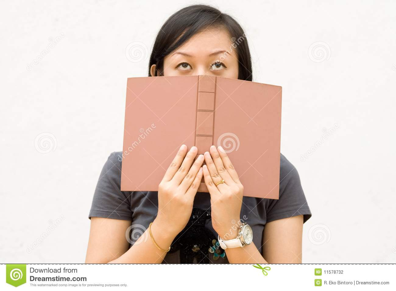 Book Covering Face : College student covering her face with book stock