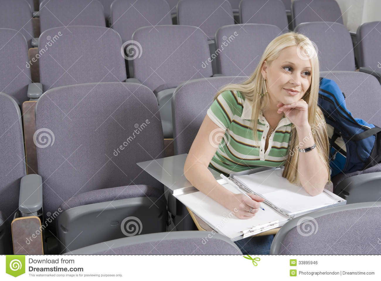 College Student Writing In Lecture Hall