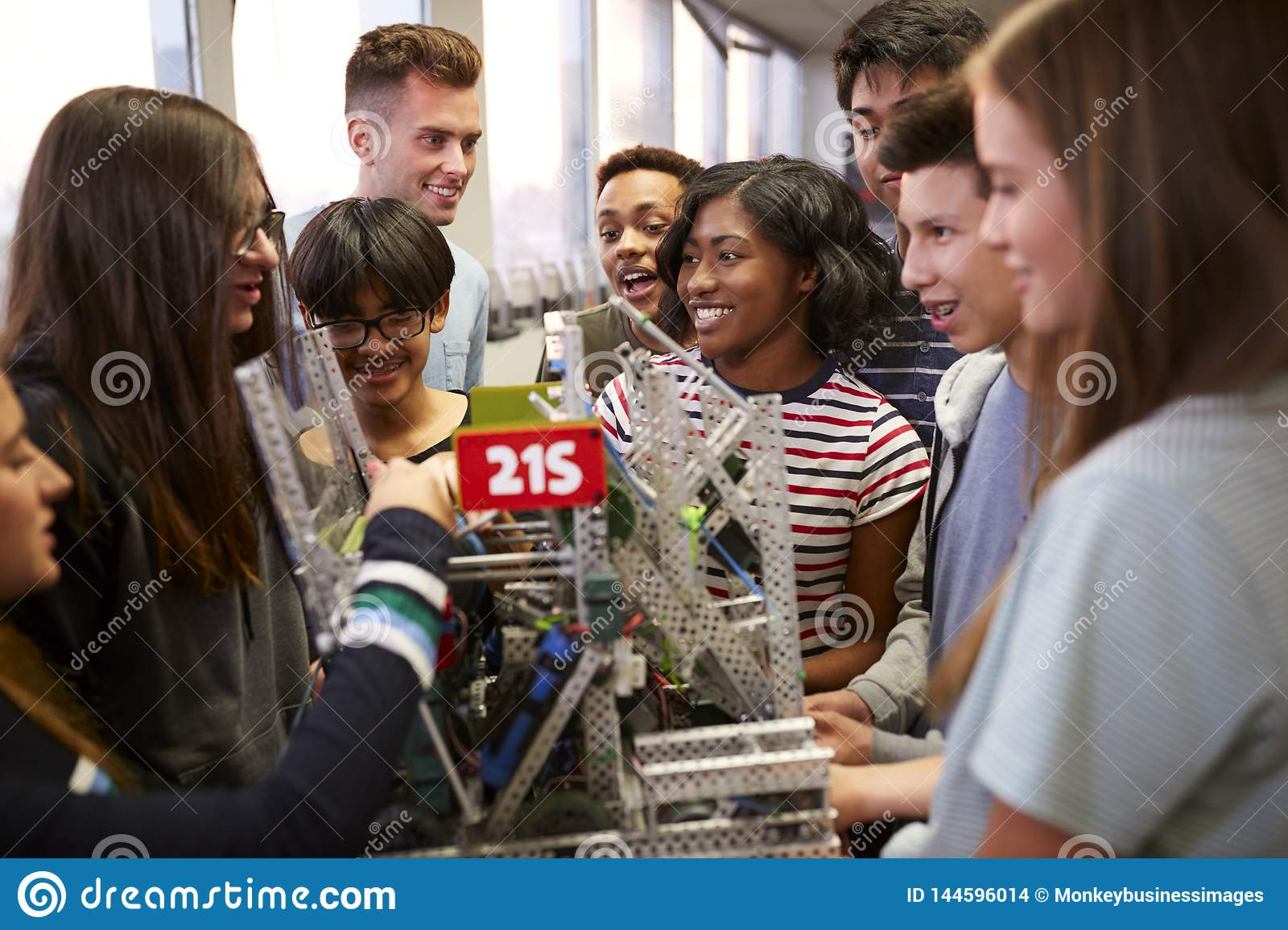 College Students With Teacher Holding Machine In Science Or Robotics Class