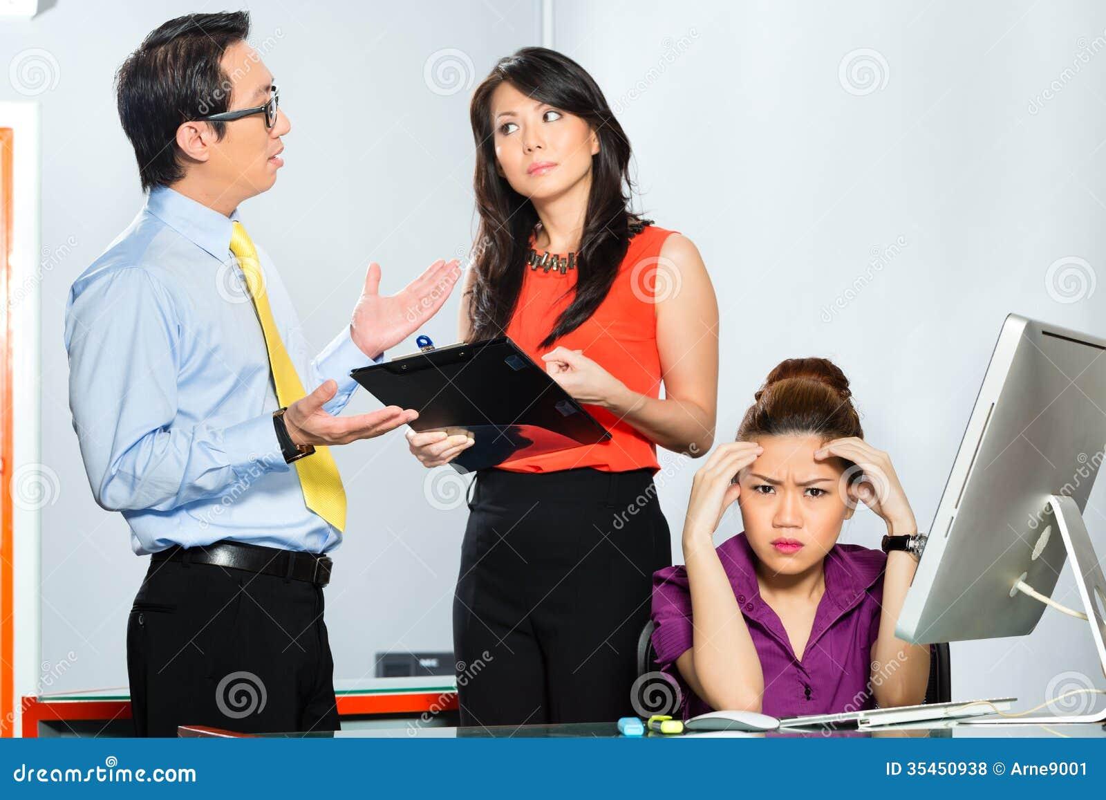 Colleghi asiatici che assalgono o che opprimono impiegato