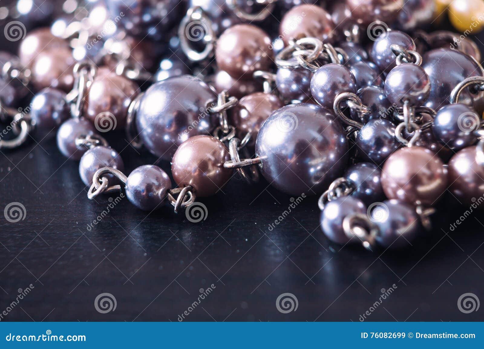 Collier gris et rose de perle sur un fond foncé avec le reflecti