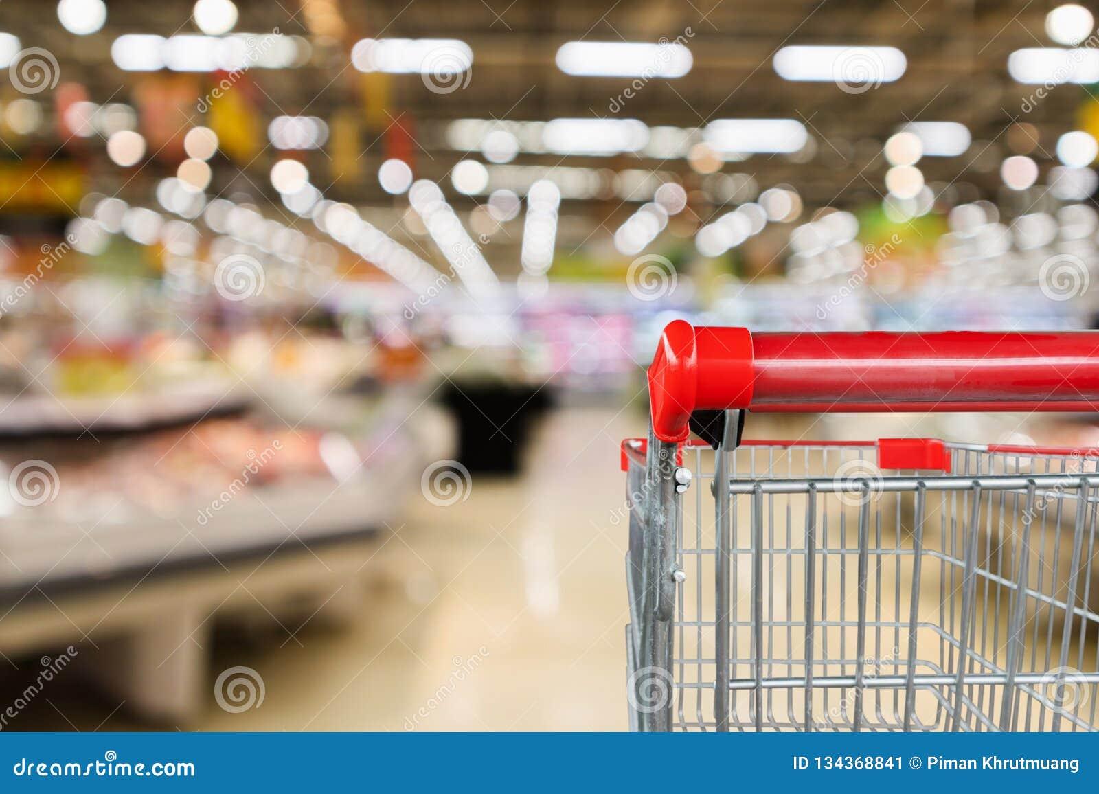 Colmado del supermercado con el fondo defocused interior de los estantes de la fruta y verdura con el carro de la compra vacío