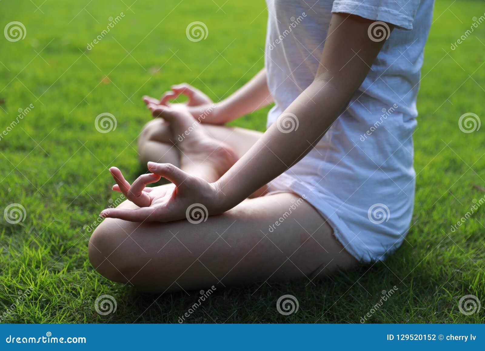 Colocación de mentira del chino asiático del primer en el césped de la hierba que piensa para hacer actitud de la yoga en la medi