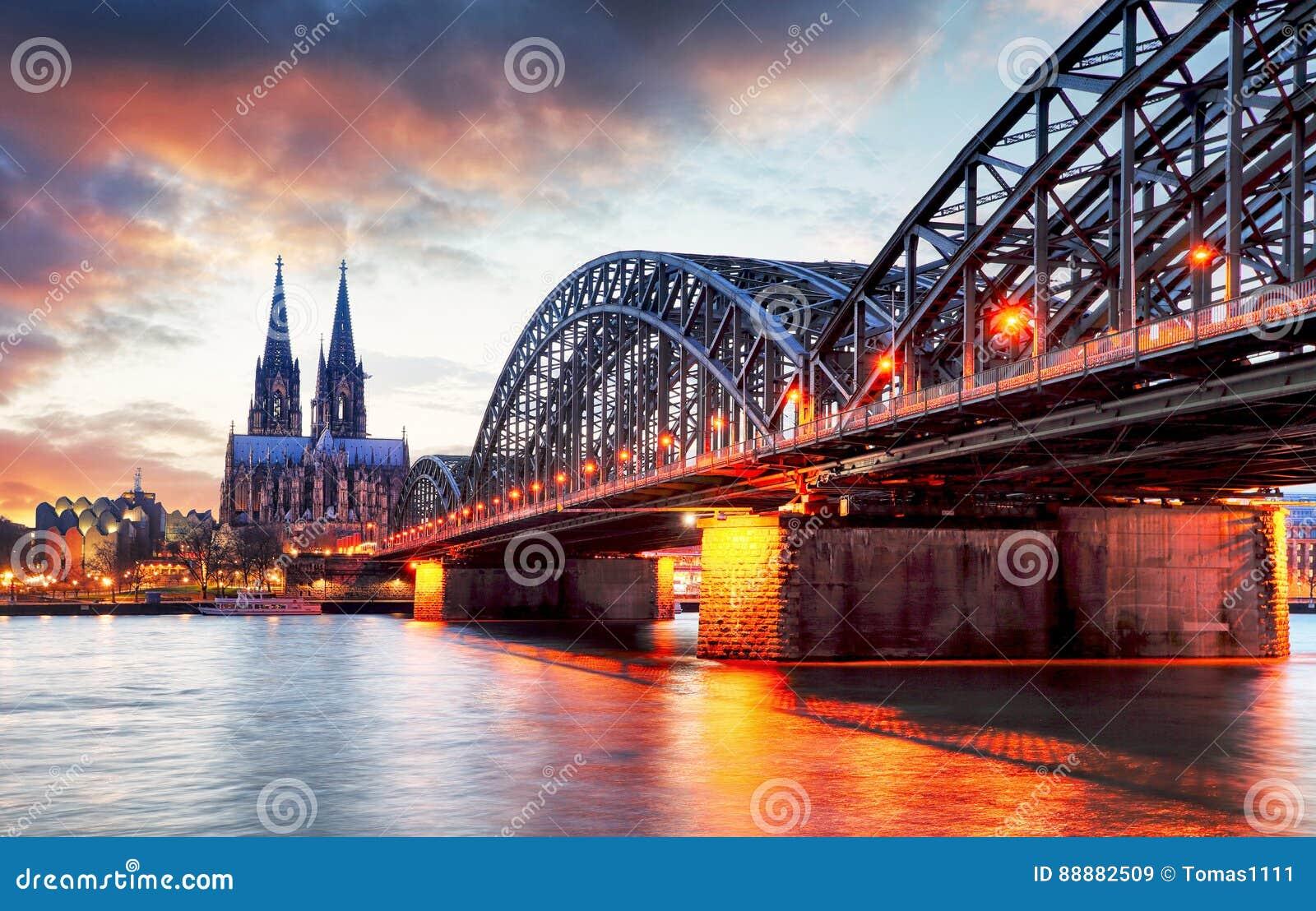 Cologne domkyrka och Hohenzollern bro på solnedgången - natt