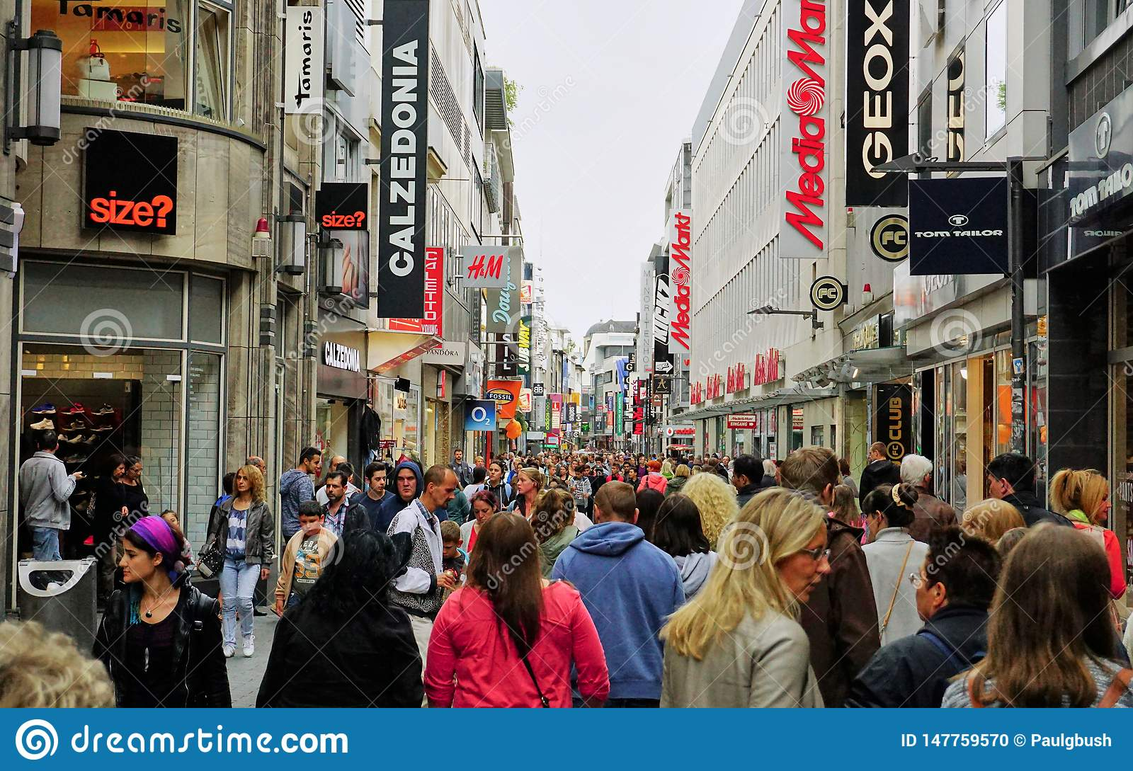 Diverse crowd fills the main shopping district street in Cologne, Germany