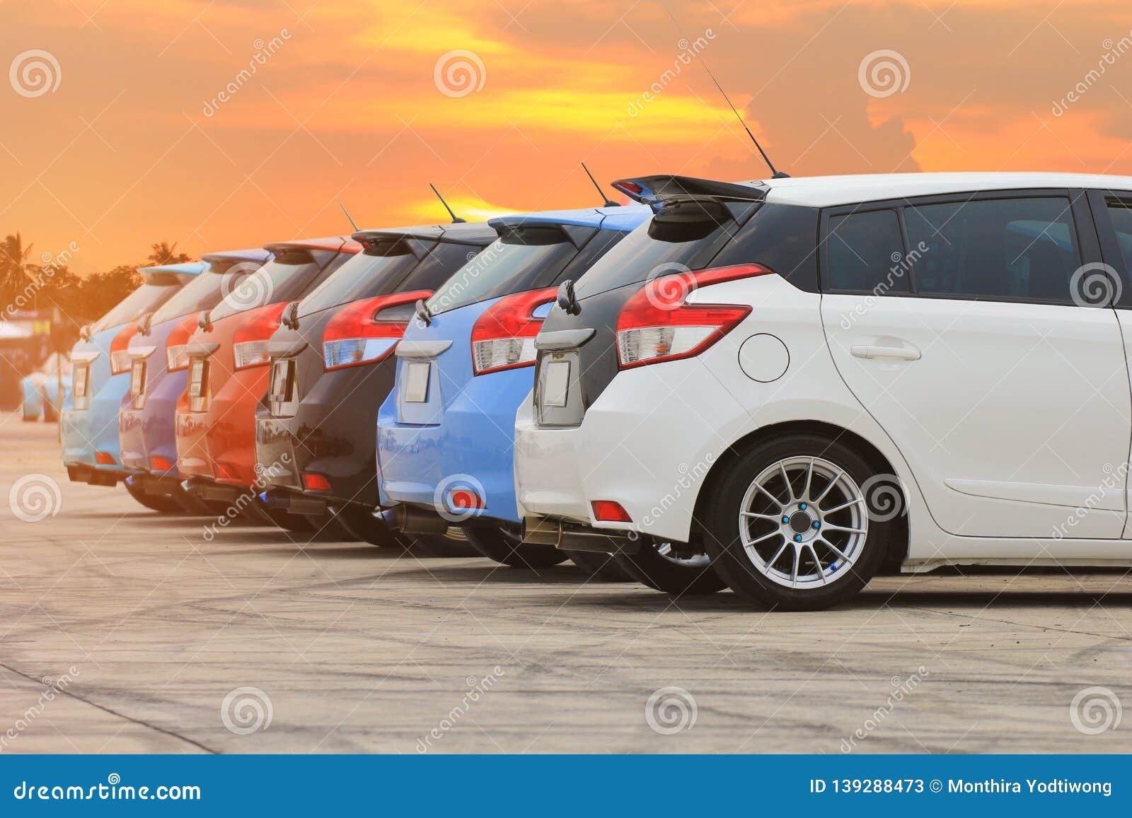 Coloré des voitures dans le parking sur le fond de coucher du soleil