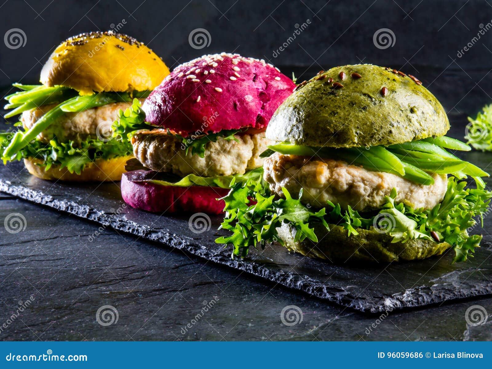 Coloré les hamburgers verts, jaunes et pourpres sur l ardoise embarquent, slate le fond