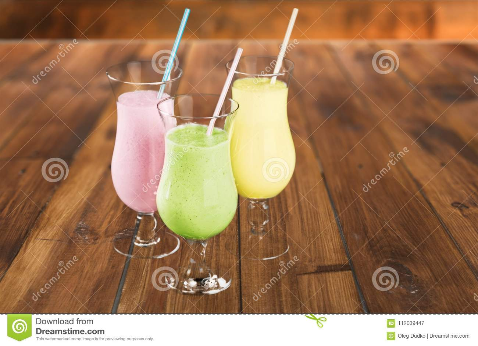 Colorful healthy milkshakes in glasses on table