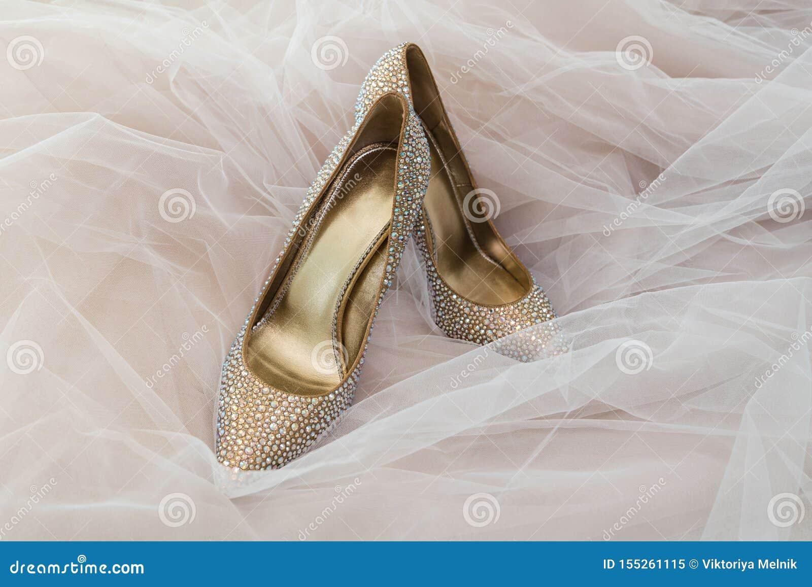 Color de oro de la novia de los zapatos de la boda con las piedras en el fondo de casarse Tulle