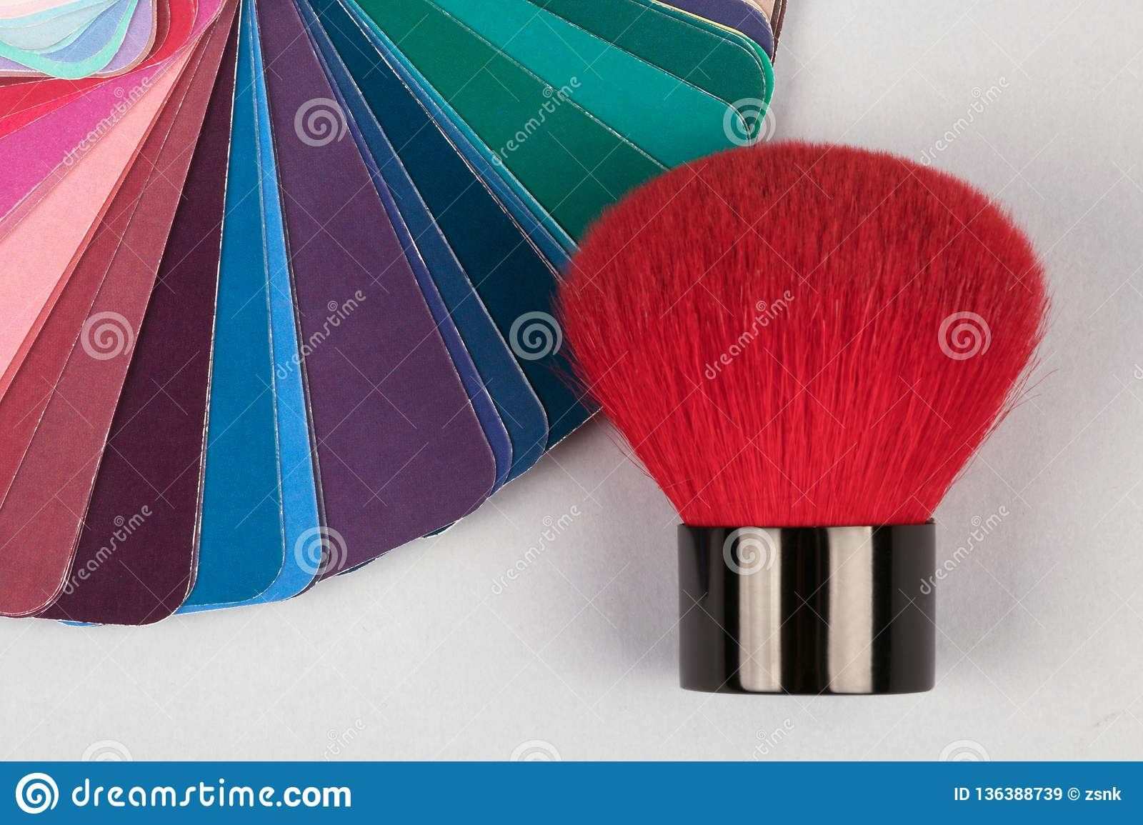 Color fan deck with samples of various paints with red brush for makeup
