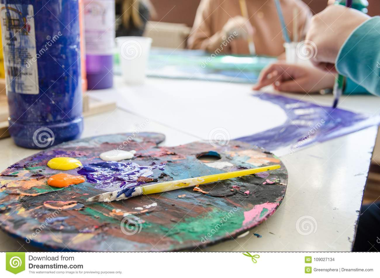 Color palette and a brush in foreground with students painting in class out-of-focus in the background