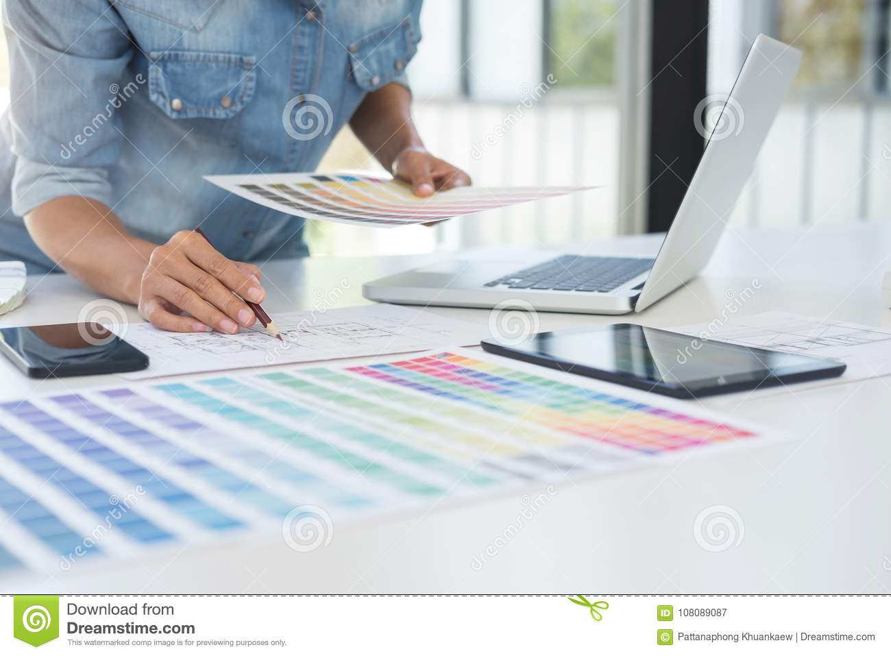 Color samples, colour chart, swatch sample, Graphic designer being selecting Color table and graphics tablet, pen at workplace wi