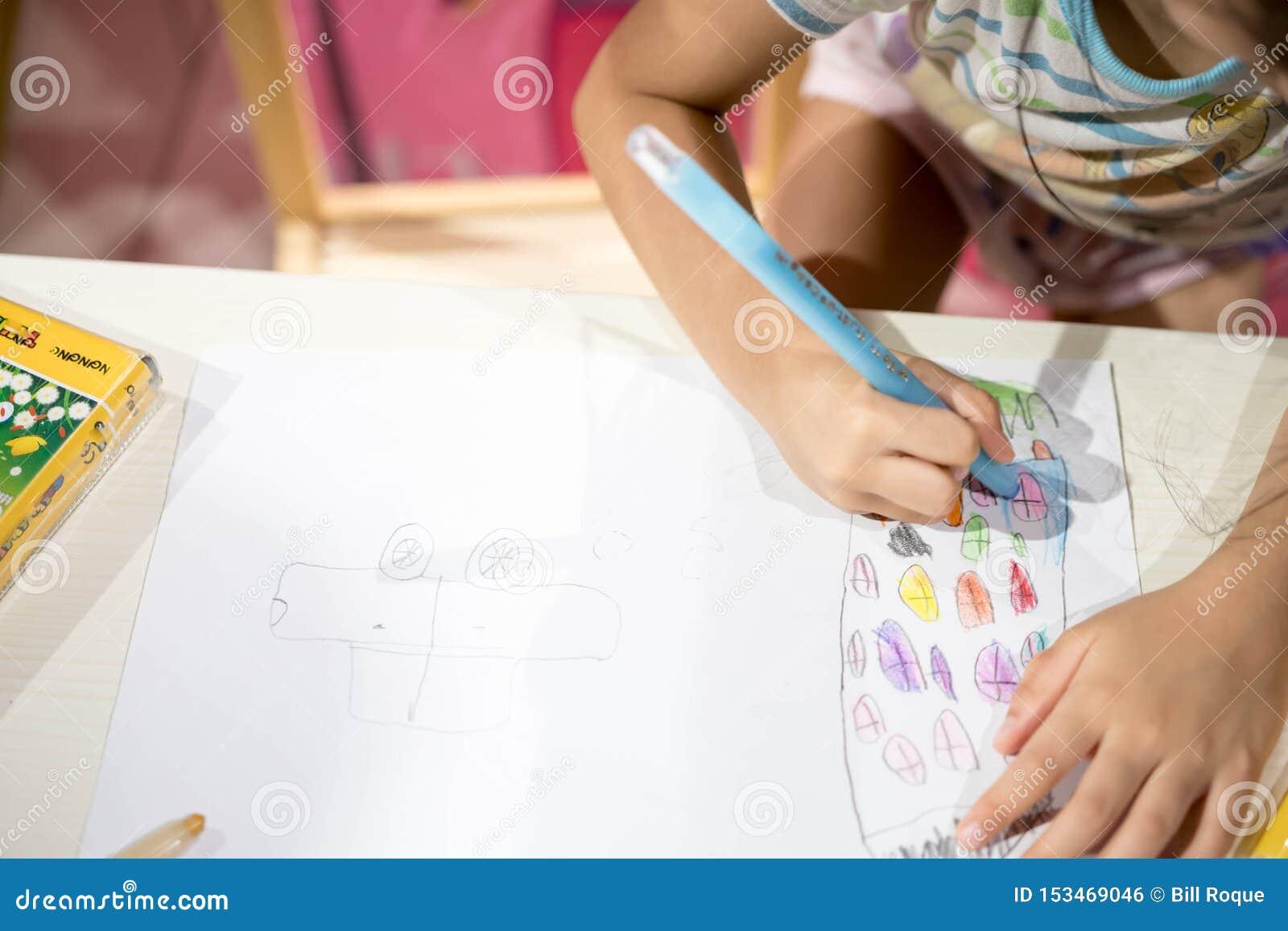 Coloração do desenho da escrita da criança no papel usando o pastel