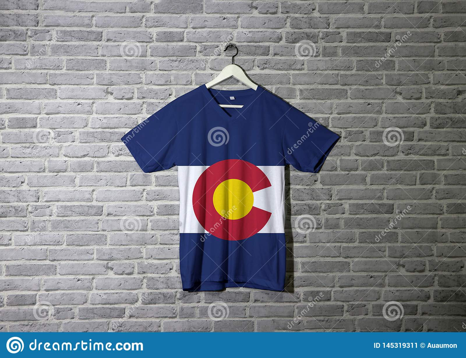 Colorado flag on shirt and hanging on the wall with brick pattern wallpaper. The states of America