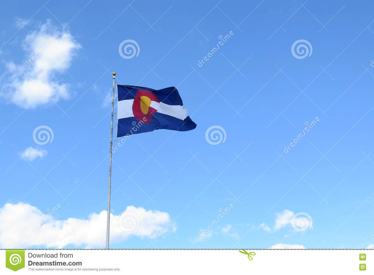 Colorado Flag waving in the wind against a blue cloudy sky