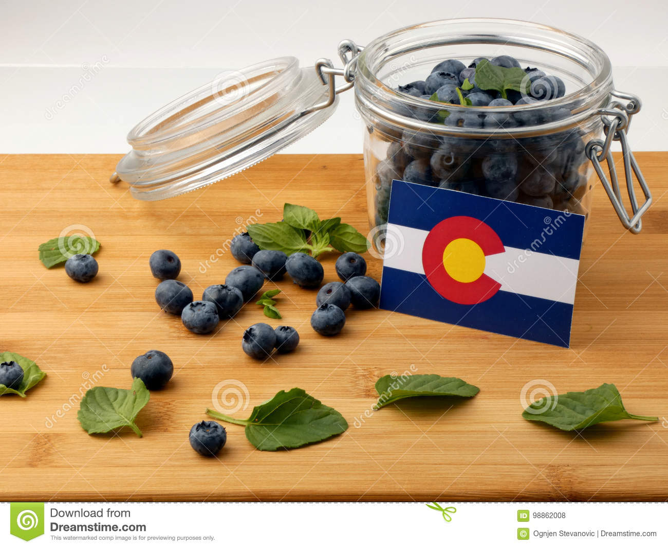 Colorado flag on a wooden plank with blueberries on whi