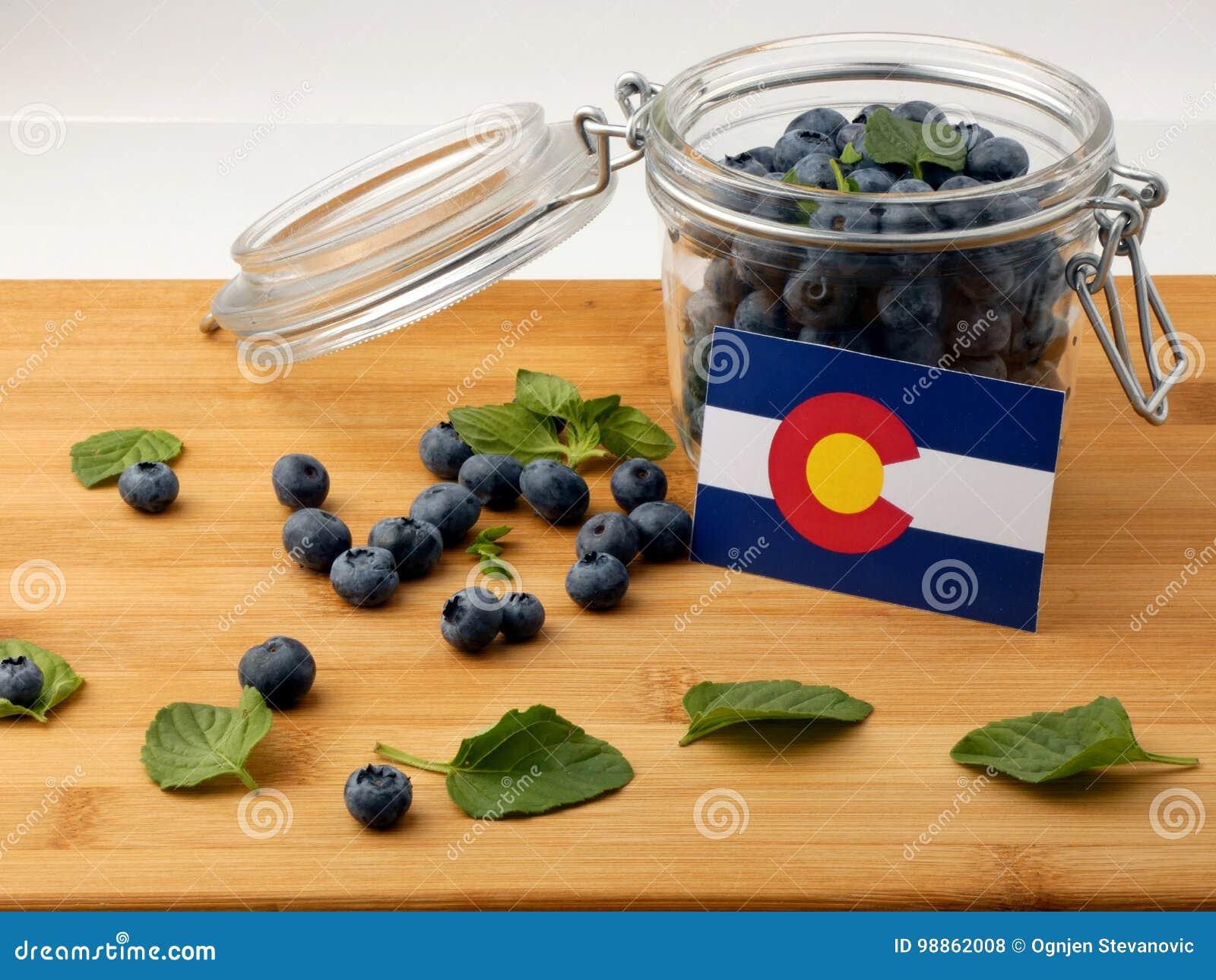 Colorado-Flagge auf einer hölzernen Planke mit Blaubeeren auf whi