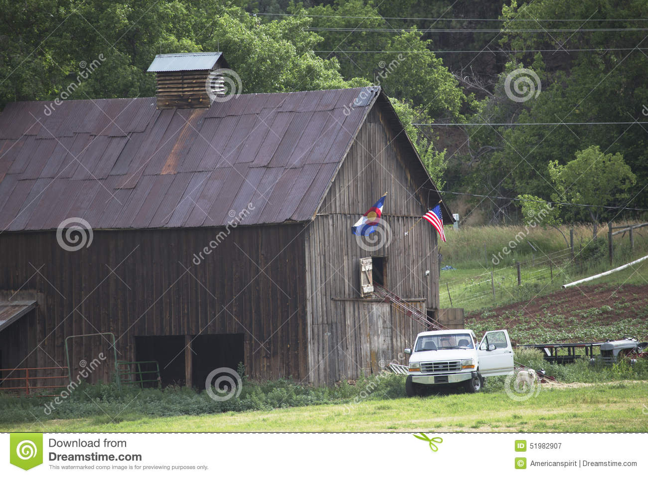 Colorado and US Flag hang on barn with white pickup truck, Colorado, USA