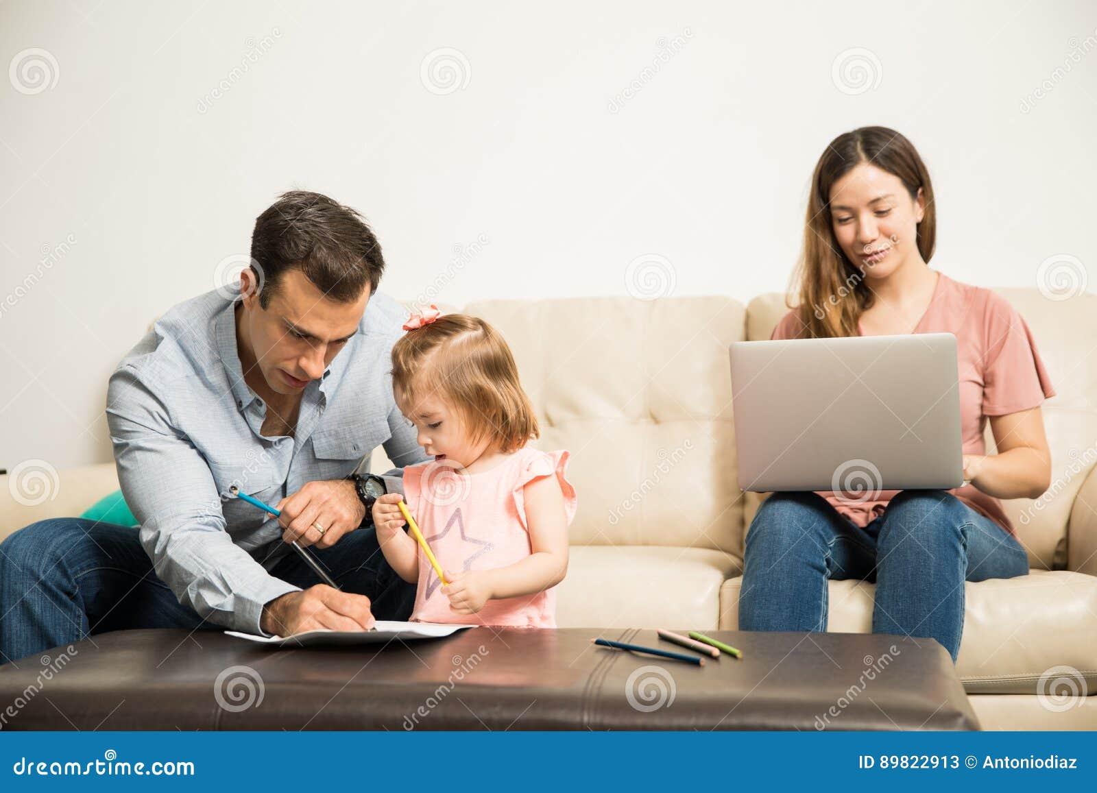 Colorante Con El Papá Mientras Que La Mamá Trabaja Imagen de archivo ...