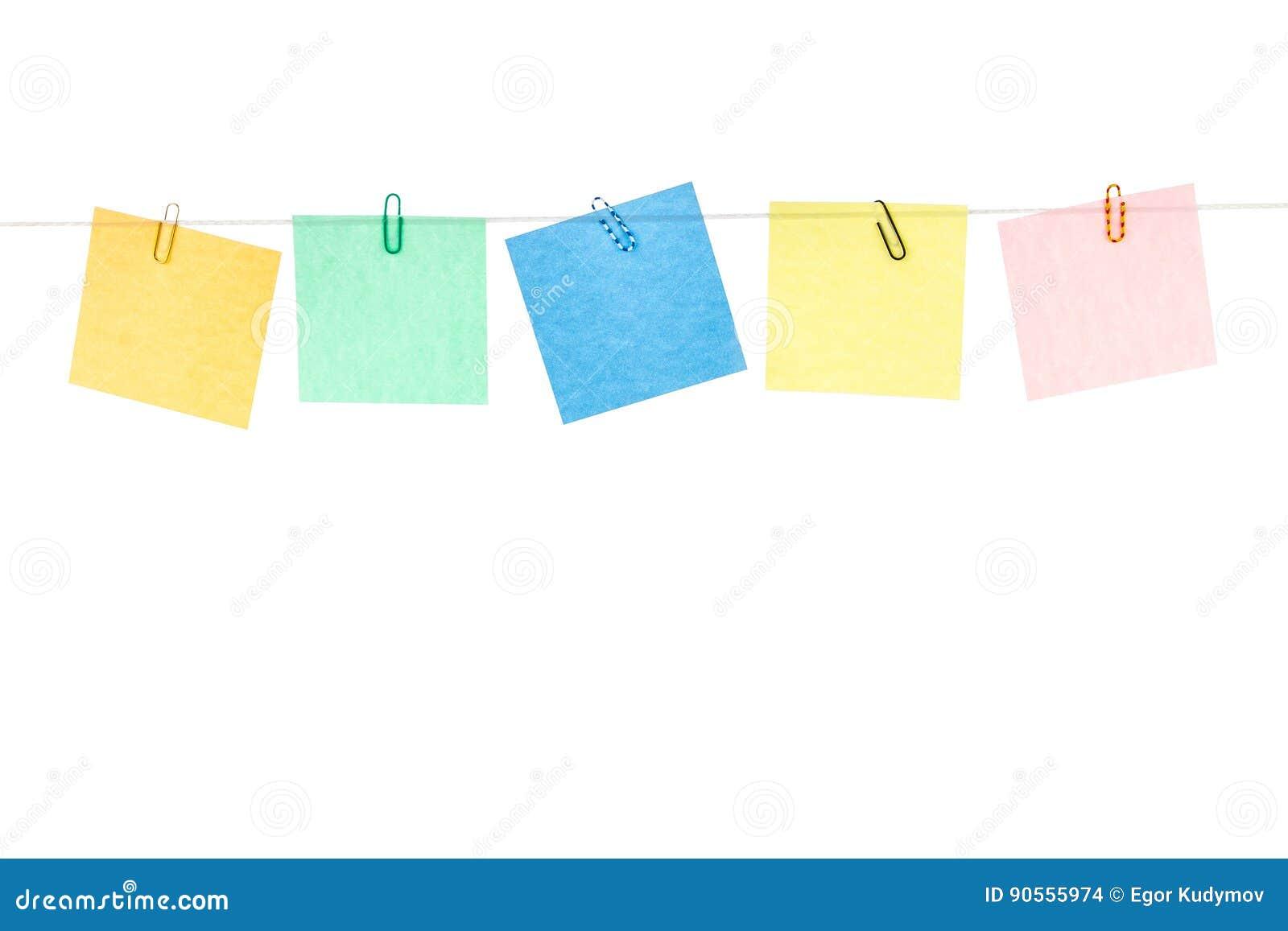 Coloreado etiquetas engomadas amarillas, verdes, azules, rojas con los clips de papel que cuelgan en una cuerda
