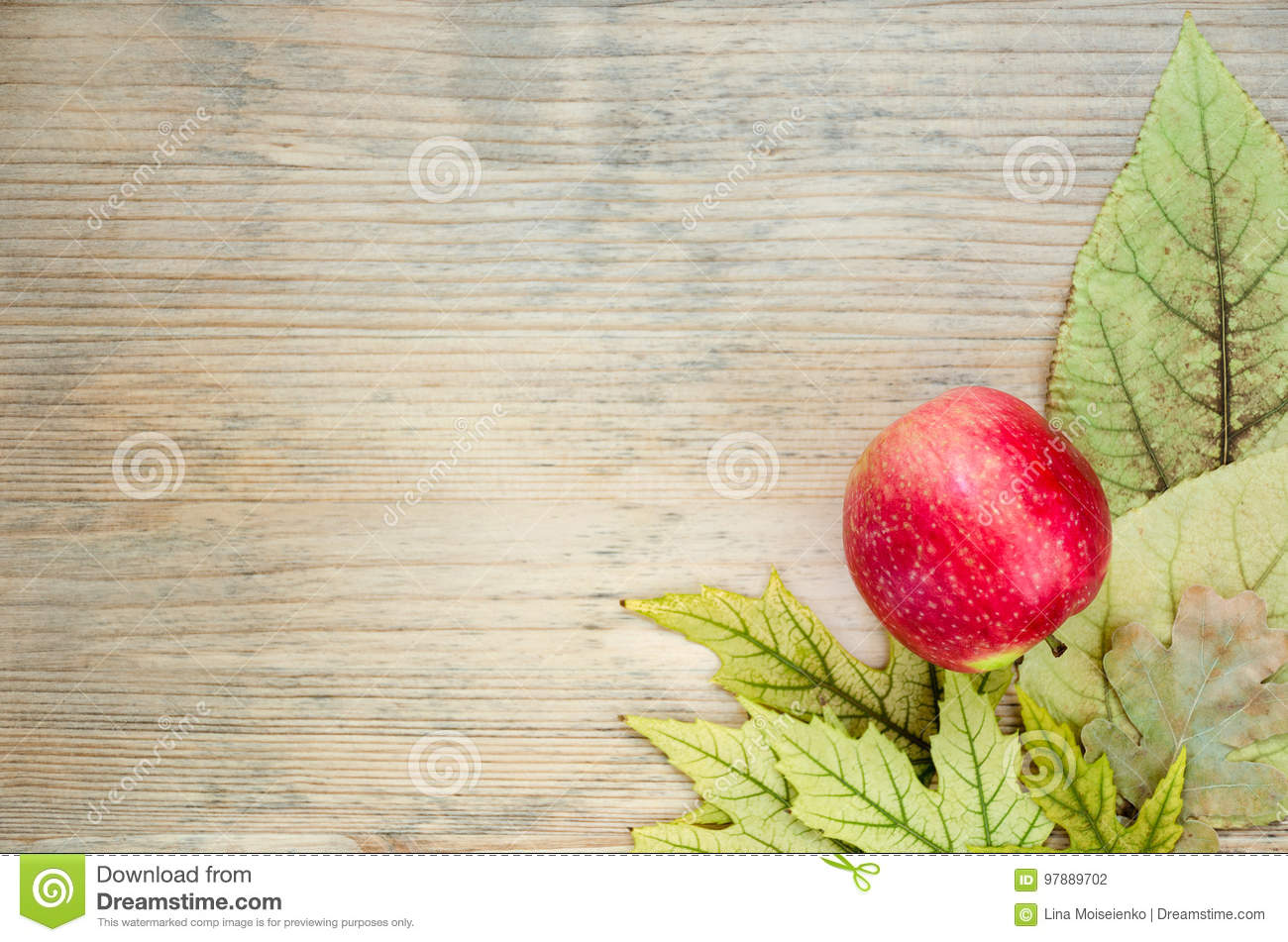 Colored autumn postcard - corner decorated with ripe red apple on yellow autumn leaves. Wooden background.