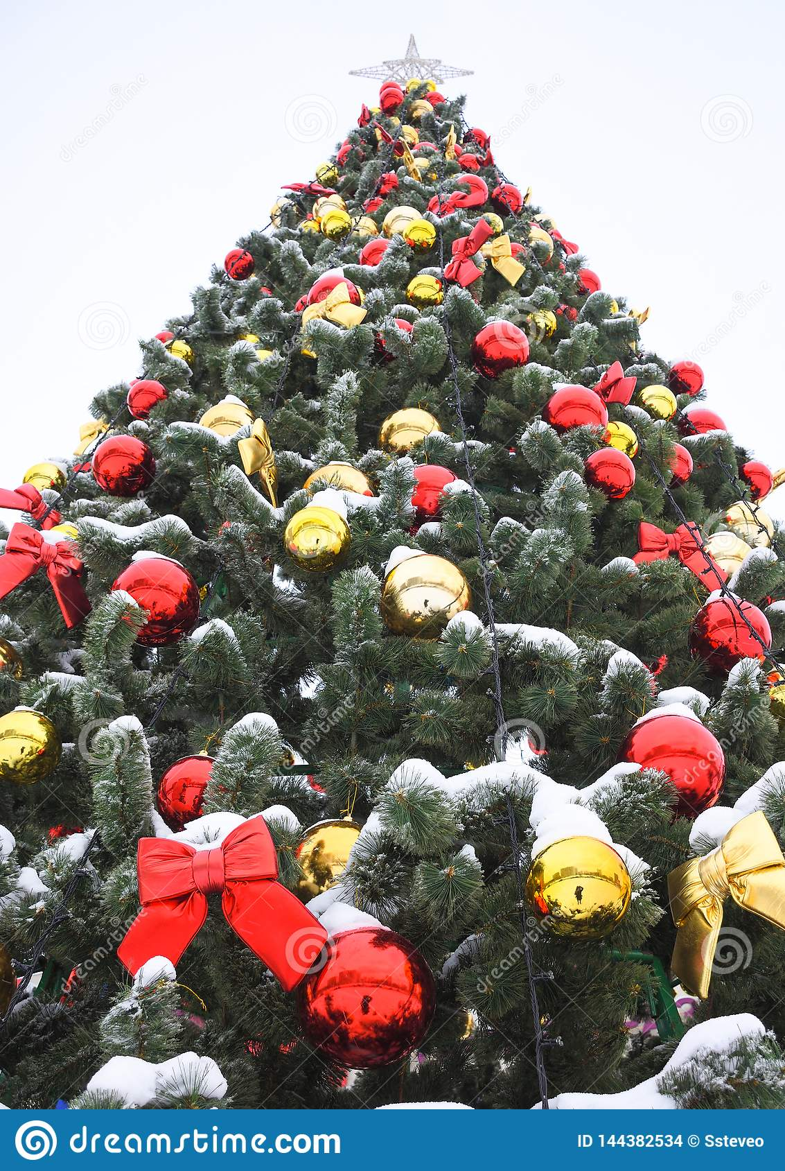 Colored balls and red bows on xmas tree