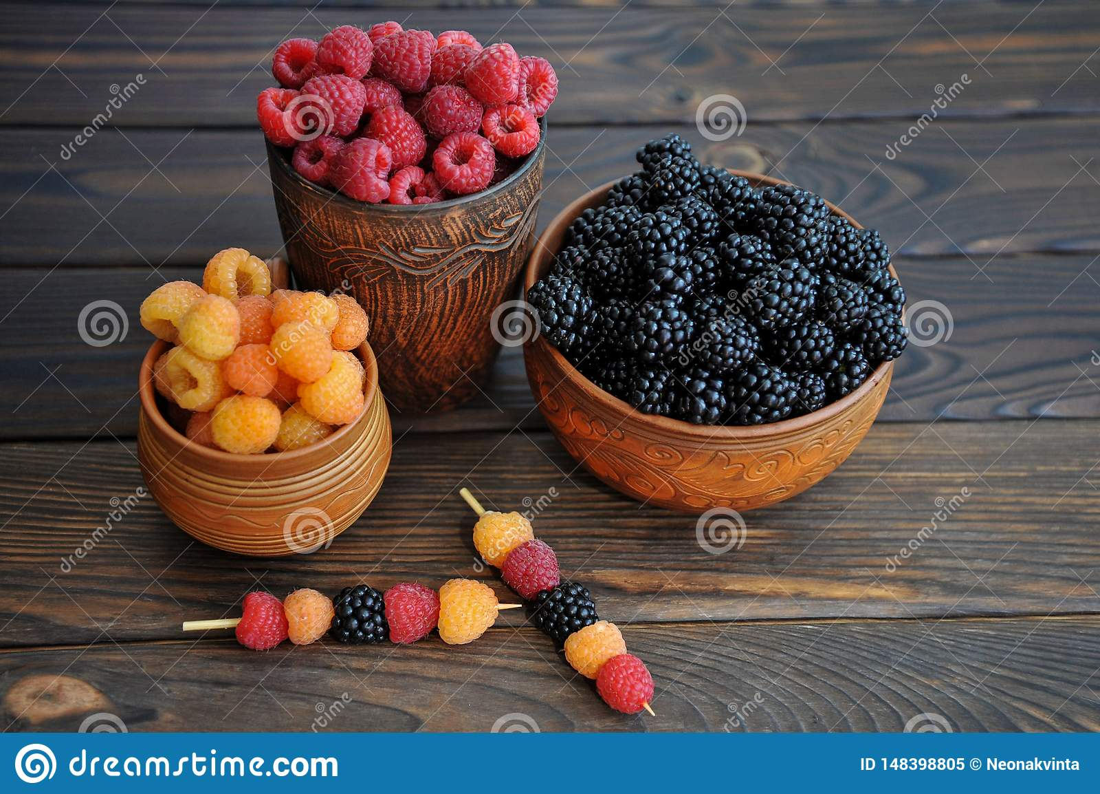Colored berries of red, yellow and black raspberries or blackberries in earthenware on a table
